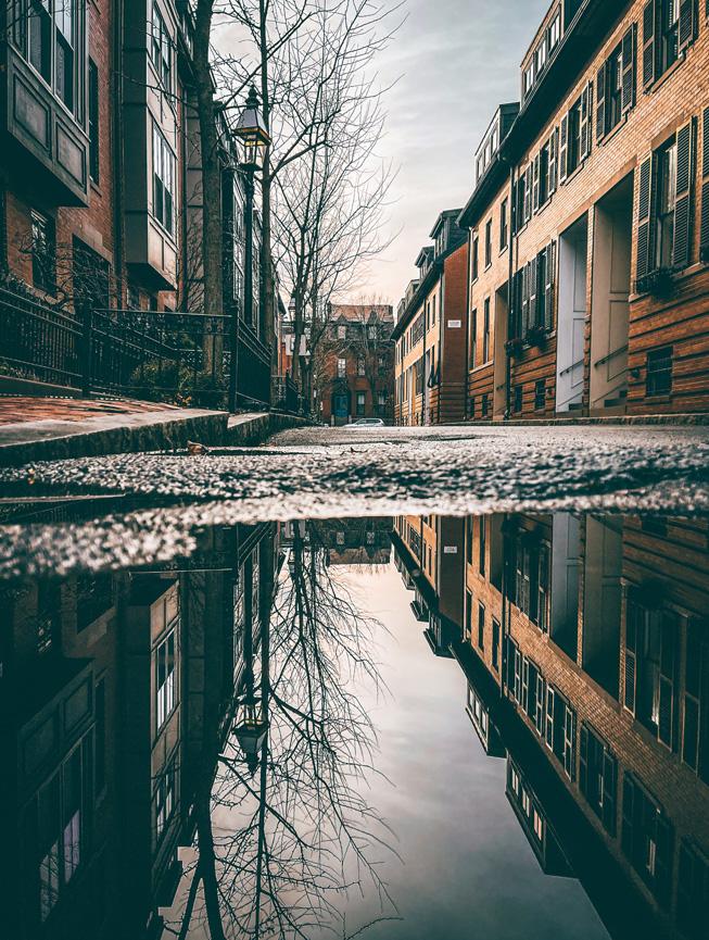 街上一大片水洼倒映出街道四周景象及上方天空。