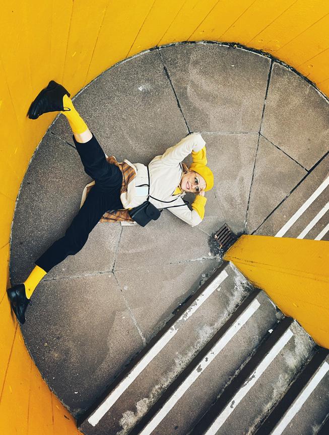 一个人在有着黄色墙壁的楼梯间平台上摆出姿势。