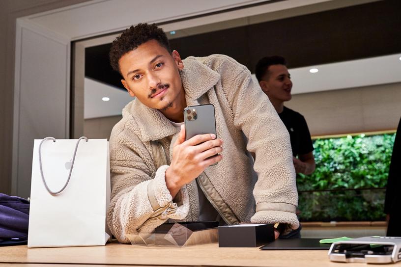 Apple Champs-Élysées 店中手握 iPhone 11 Pro Max 的顾客。