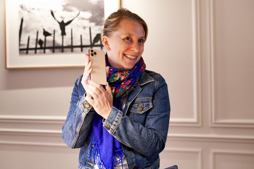 Apple Champs-Élysées 店内手握 iPhone 11 Pro 的顾客。