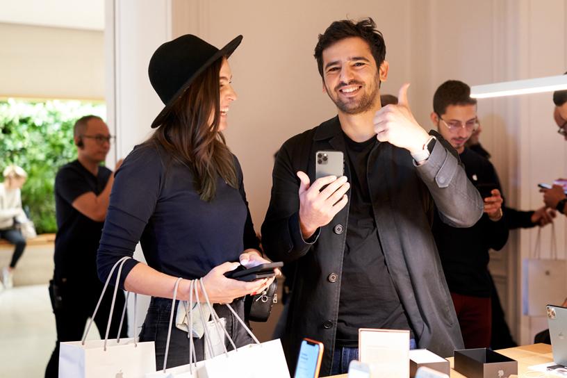 在 Apple Champs-Élysées,一名 Apple 员工正在帮助手持 iPhone 11 Pro 的顾客了解产品。