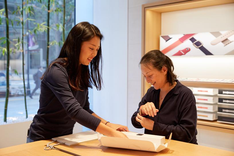 Apple Marunouchi 店内,一名 Apple 员工正在协助顾客试戴 Apple Watch Series 5。