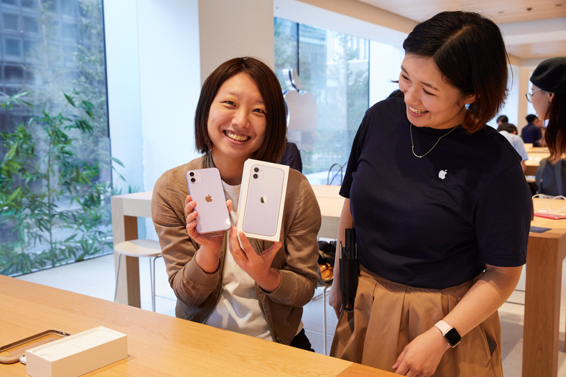在 Apple Marunouchi 店内,顾客手拿 iPhone 11 及包装盒,旁边是一位 Apple 员工。