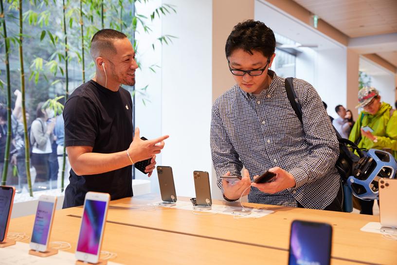 Apple Marunouchi 店内,一名 Apple 员工与正在体验 iPhone 11 Pro 的顾客进行交谈。