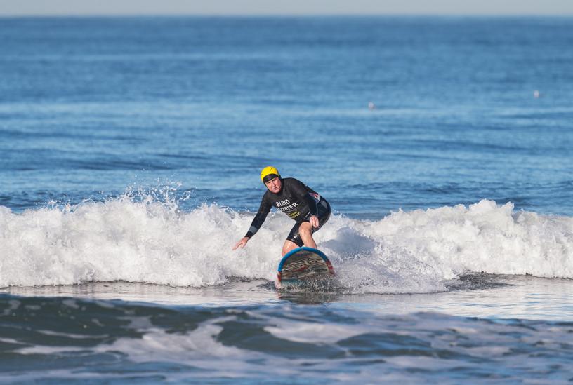 "Leason 身穿正面印着""盲人冲浪者""字样的滑水服,示意队友他需要一些空间。"