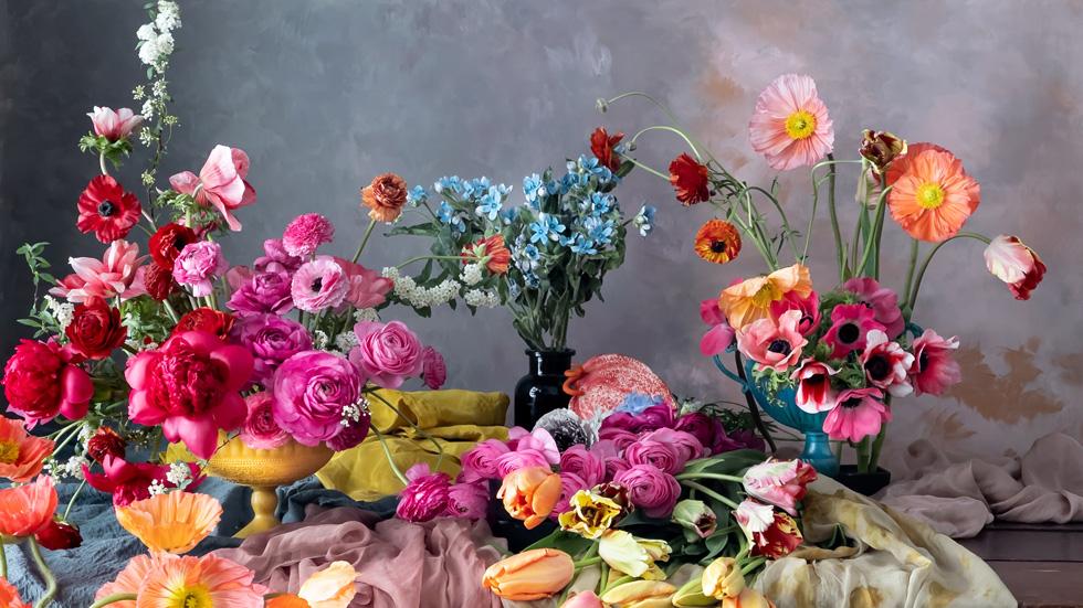 桌子上摆放有多个插花作品。