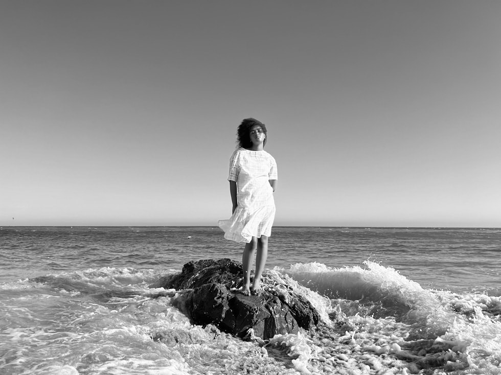 使用 iPhone 13 Pro 广角镜头配合传感器位移式 OIS 功能拍摄的站立在海边的女子。