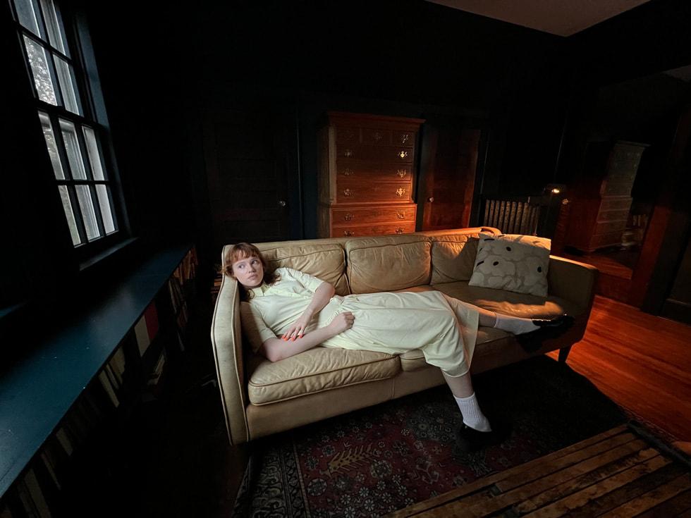 使用 iPhone 13 Pro 超广角镜头拍摄的躺在沙发上的女子。