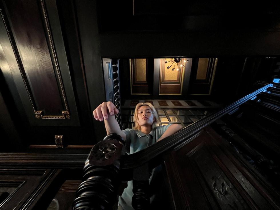 使用 iPhone 13 的超广角摄像头拍摄的深色楼梯上的男子人像。