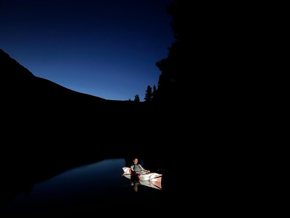 使用 iPhone 13 的广角摄像头夜间模式在夜间拍摄的独木舟中的男子。