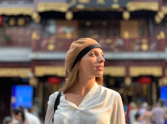 一位戴贝雷帽的女士在街头向左看。