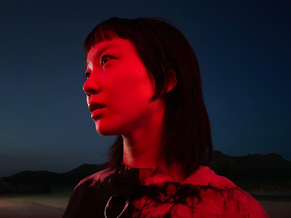 使用 iPhone 12 为一位年轻女子拍摄的夜间模式人像照。