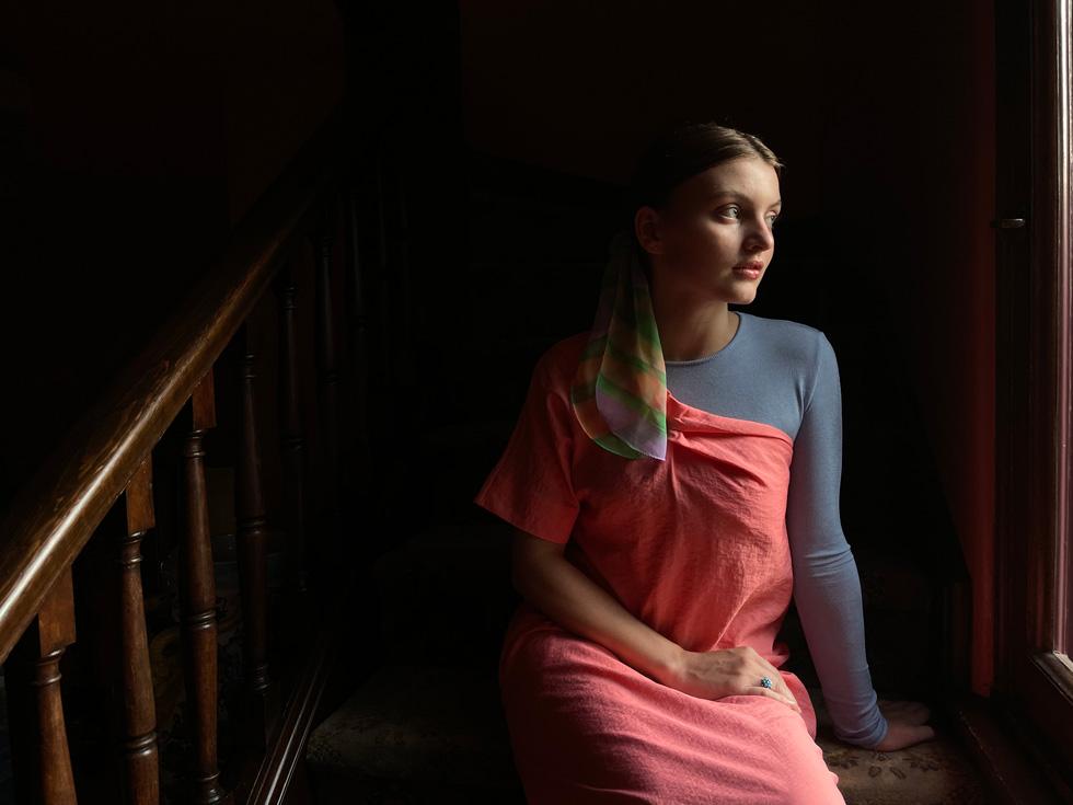 使用 iPhone 12 在昏暗室内为一位年轻女子拍摄的人像照。