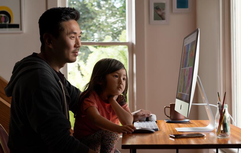 一对父女在家中的 iMac 上浏览照片。