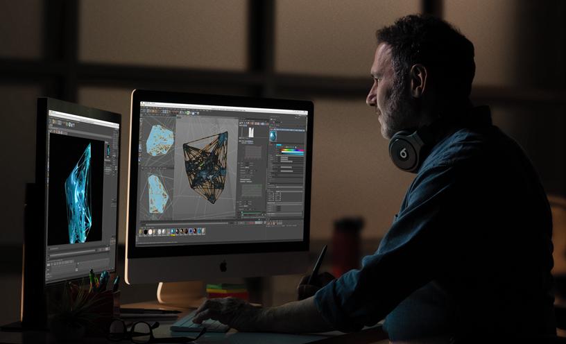 专业人士在 iMac 和辅助监视器上查看三维图像。