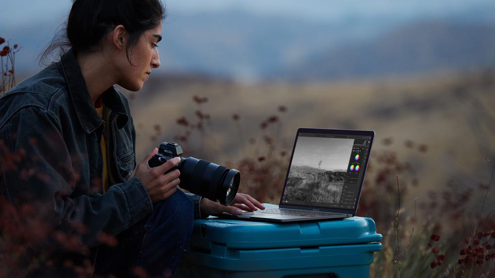 一名摄影师正在使用她的相机以及配备 M1 芯片的 MacBook Air。
