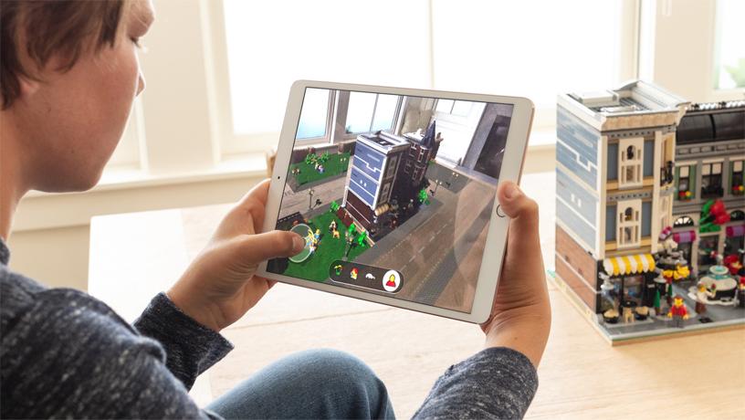 房间里一个男孩手持 iPad 坐在一栋乐高建筑前,iPad 屏幕上显示的是 LEGO AR City。