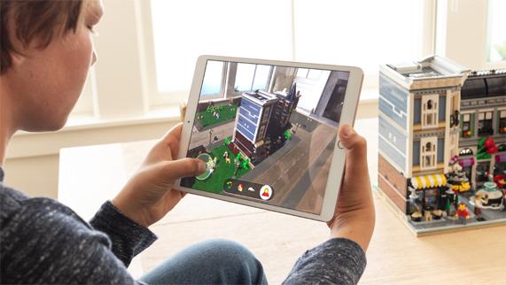 小男孩坐在房间里,手握 Apple Pencil 看着屏幕上的 LEGO AR City。