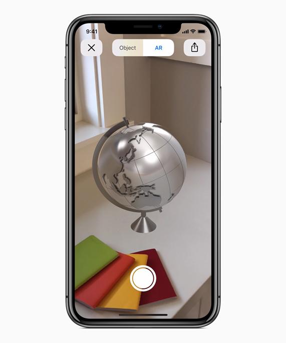 iPhone X 在展示桌面上一台由增强现实技术打造的地球仪。