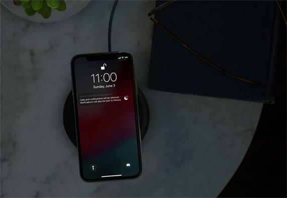 黑暗房间内使用无线充电器的 iPhone 屏幕上显示勿扰模式。