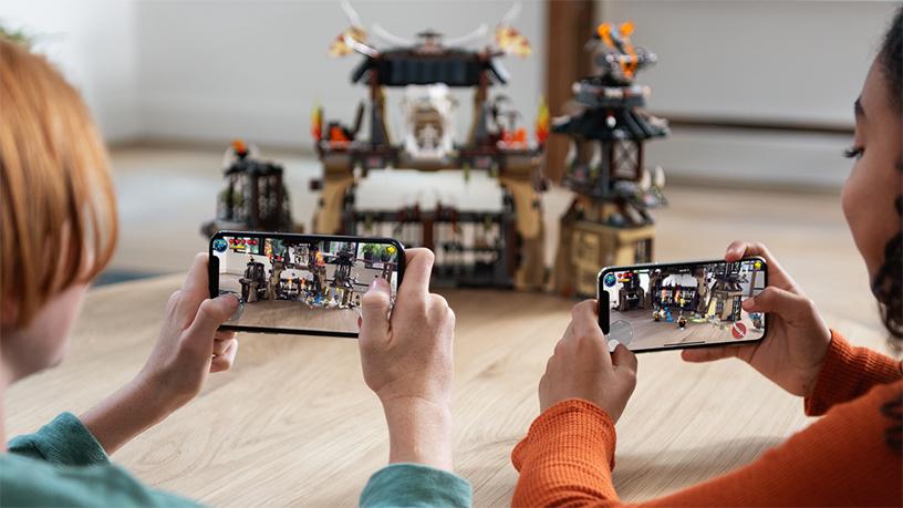 两个孩子正在玩 iPhone 增强现实游戏。