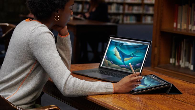 一位女性正在通过随航功能使用 MacBook 和 iPad。