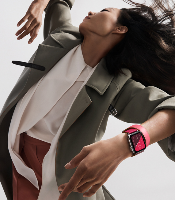 一个佩戴搭配亮丽拼色表带 Apple Watch Hermès 的女子。