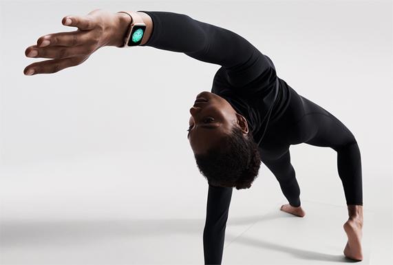 一个佩戴金色 Apple Watch Series 4 的女子正在垫子上练习瑜伽。