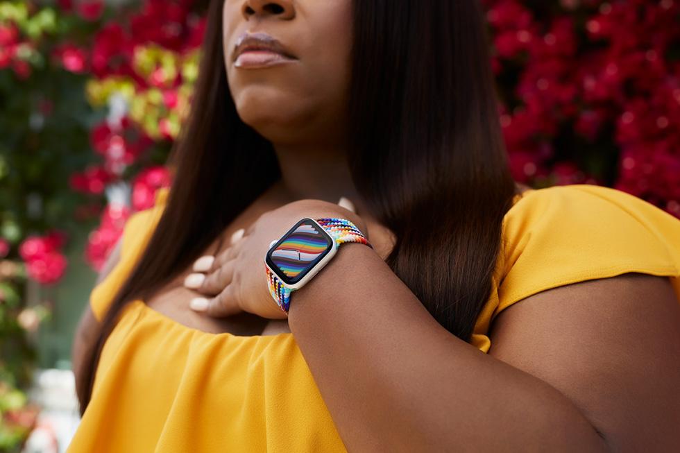 LGBTQ+ 拥护者 Dominique Morgan 佩戴 Apple Watch 彩虹版编织单圈表带和彩虹版表盘的特写图片。