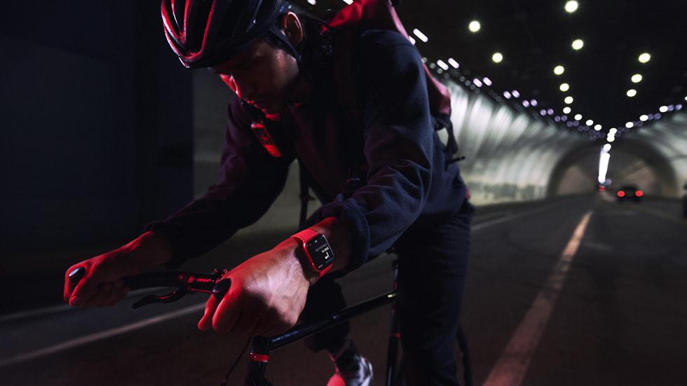 一名骑行者佩戴 AppleWatchSeries7,在夜间穿过隧道。