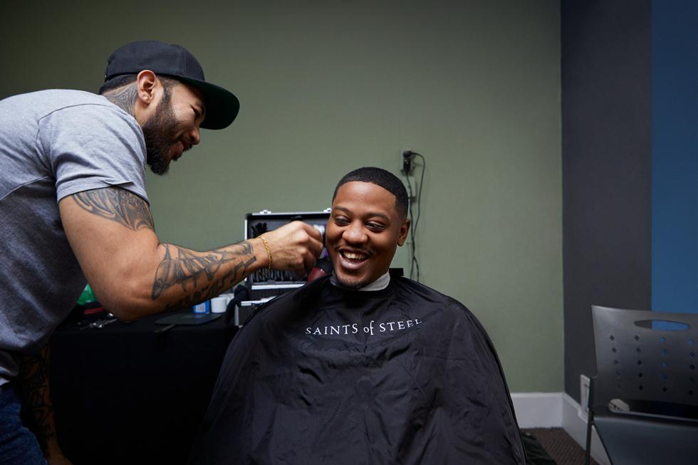 理发师正在为一个年轻人剪发。