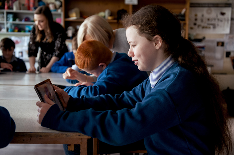 一个女孩正在教室中使用 iPad。