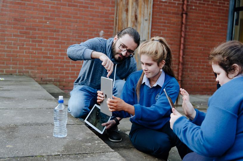 一名年轻女子正在 Apple 志愿者的协助下使用 iPad 拍照。