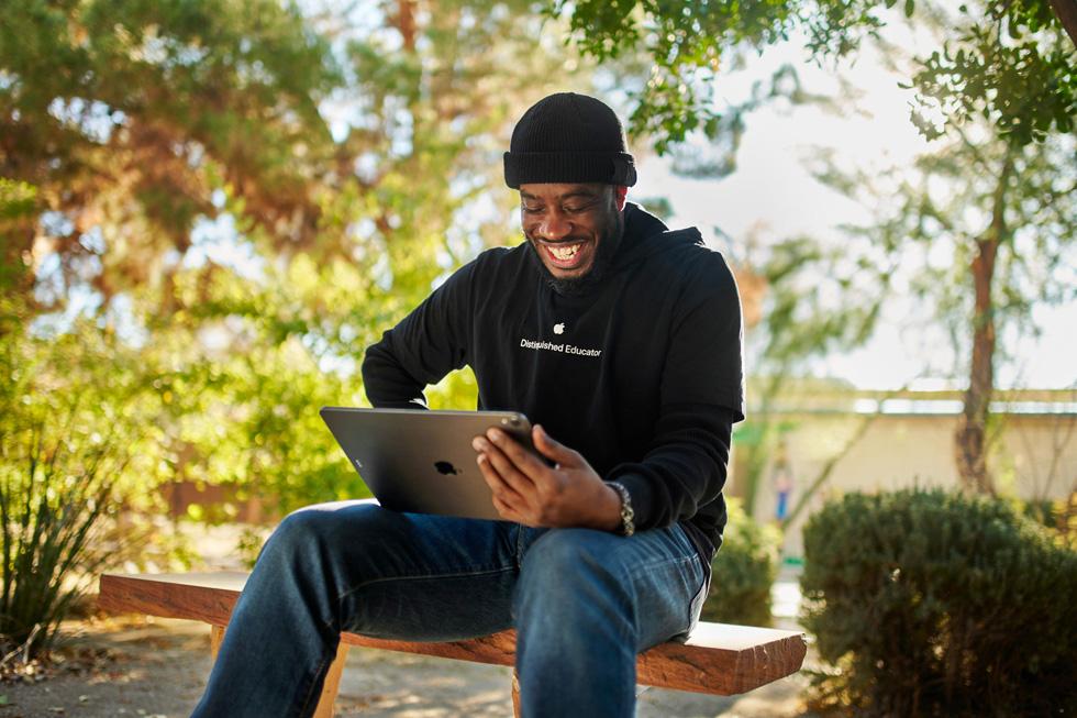 Mike Lang 坐在室外使用 iPad。