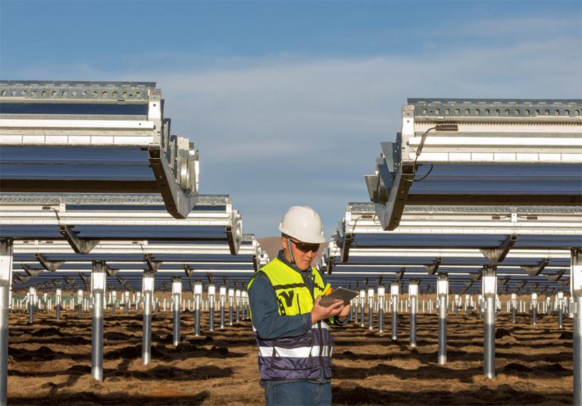 中国四川省光伏电站的工人站在太阳能电池前。