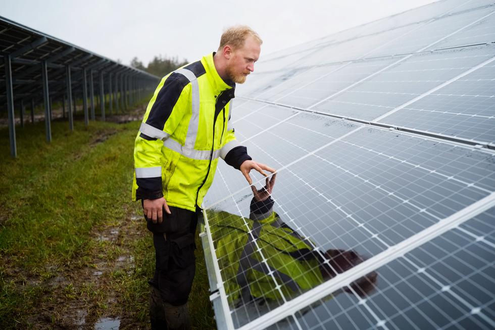 一名工人正在检查一个太阳能电池阵。